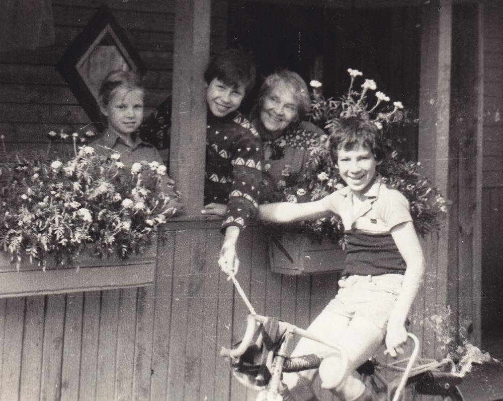 """A. Liobytė su anūku Jonuku ir dailininko M. Vilučio vaikais savo sodyboje """"Gyvatynėje"""". Šniūrai, Molėtų r., 1983 m."""