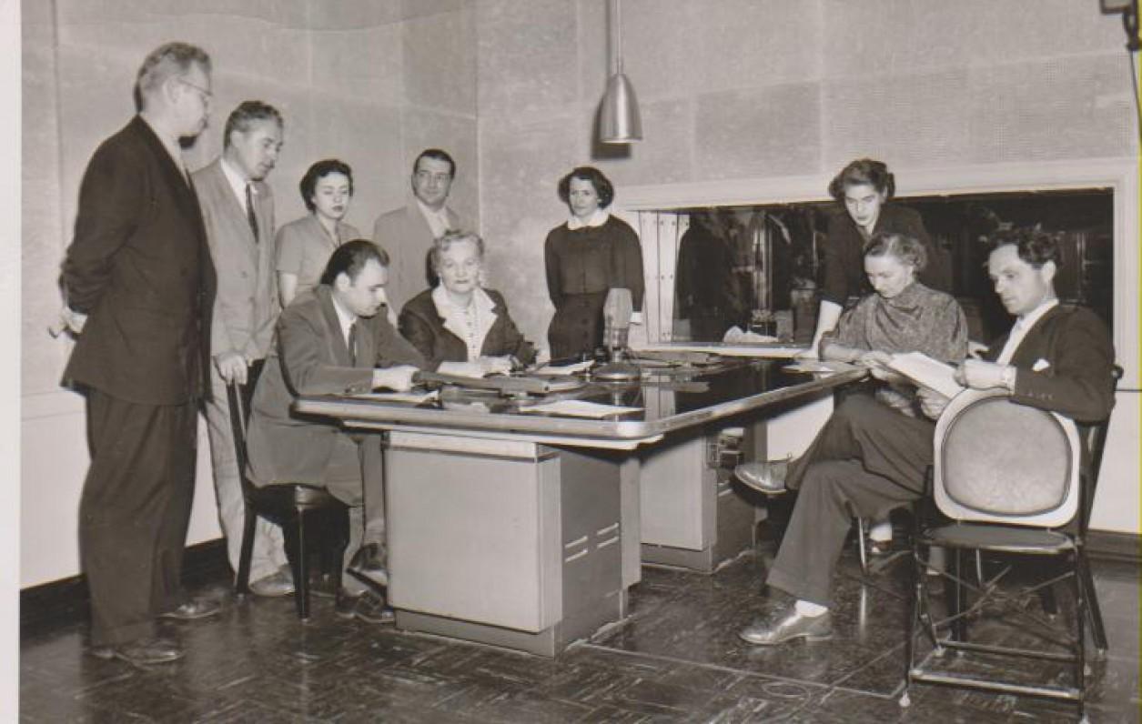 """Dalia Sruogaitė (sėdi prie stalo) radijo stotyje su programos """"Pelkių žiburėlis"""" dalyviais. Čikaga, 1954 m."""