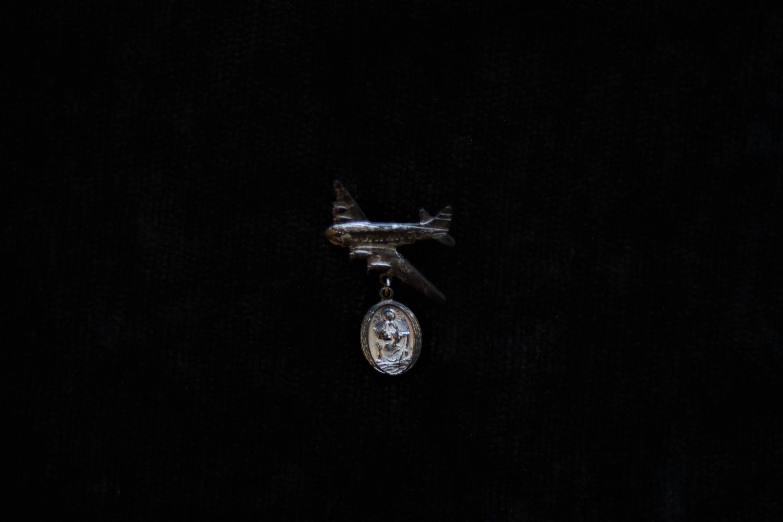 Ženklelis, skirtas keliaujantiems (lėktuvas su prikabintu medalikėliu)