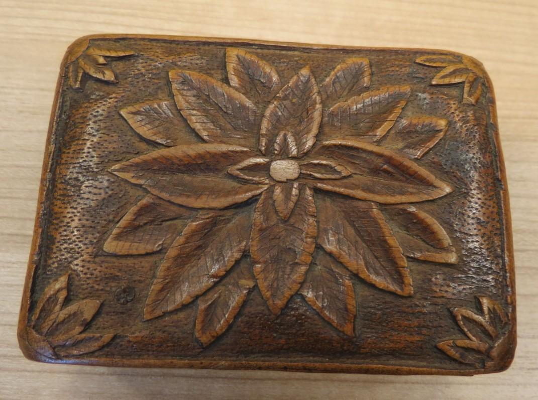 Medinė tabokinė – dėžutė, cigaretėms laikyti. Rankų drožinėjimas. Vienoje pusėje gėlės motyvo ornamentas, kitoje – lietuviško ąžuolo ornamentas