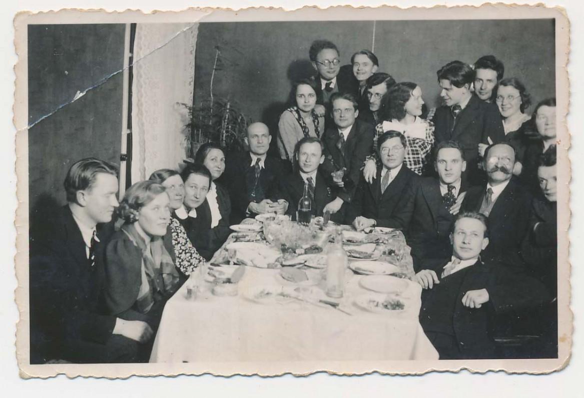 Puotoje su draugais. J. Kruminas (dešinėje viršuje) žvelgia į būsimą žmoną Onutę. Gale stalo – Kazys Jakubėnas. Apie 1938 m.