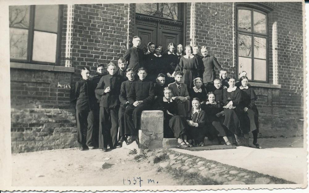 7-oji klasė su auklėtoju J. Paleku prie Vilkaviškio gimnazijos. 1936 m. K. Bradūnas sėdi šalia auklėtojo; J. Švabaitė – iš kairės trečia