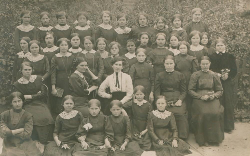"""M. Pečkauskaitė ir J. Kairiūkštytė-Tumėnienė su Marijampolės """"Žiburio"""" mergaičių progimnazijos mokinėmis. 1913 m."""