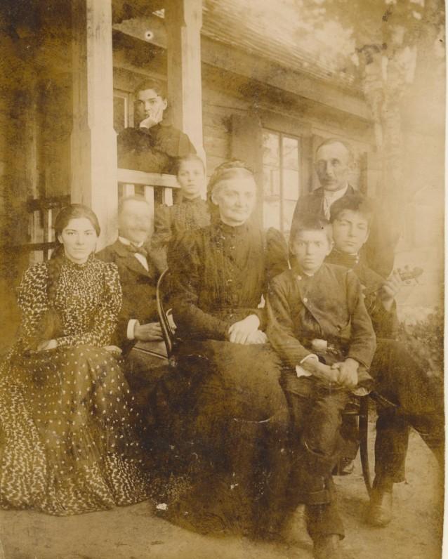 M. Pečkauskaitė (sėdi verandoje) su tėvais, seserimi, broliais ir kitais artimaisiais. Užvenčio dvare. 1896 m. Nuotrauka P. Višinskio