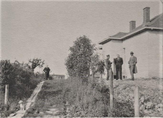 B. Sruoga, T. Reingardas, K. Penčyla ir nežinomas asmuo prie statomo namo