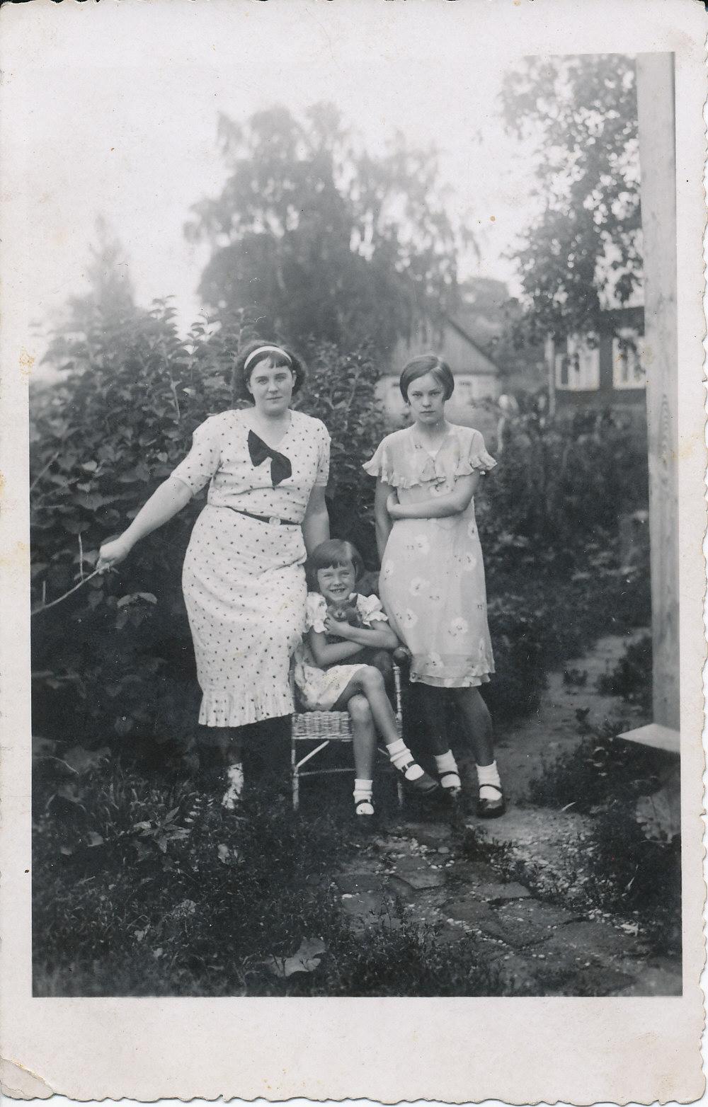 Iš kairės stovi motina J. Degutienė, pintoje kėdėje sėdi Janina su katinu, dešinėje – teta Zofija. Telšiai, apie 1935 m.
