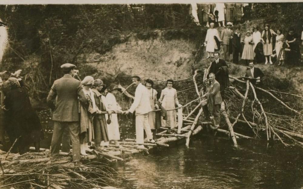 J. Eretas (baltu kostiumu, ant tiltelio), J. Paukštelis (krante, dešinėje), V. Mykolaitis-Putinas (tamsiu kostiumu). Ant kalvos, antra iš dešinės – S. Nėris