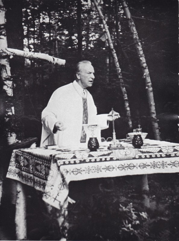 """Kun. S. Yla aukoja Šv. Mišias vaikams """"Neringos"""" stovykloje, ant improvizuoto altoriaus. Apie 1969 m."""