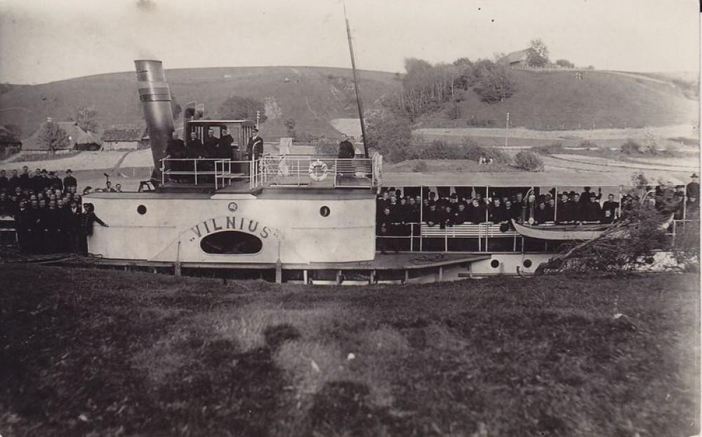 """Maironis (prie kamino) ir kiti keleiviai garlaivyje """"Vilnius"""". Apie 1930 m."""