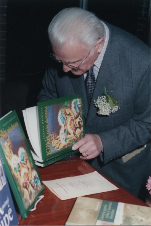 S. Džiugas pasirašo knygoje. Apie 2000 m. J. Tamulaičio nuotrauka