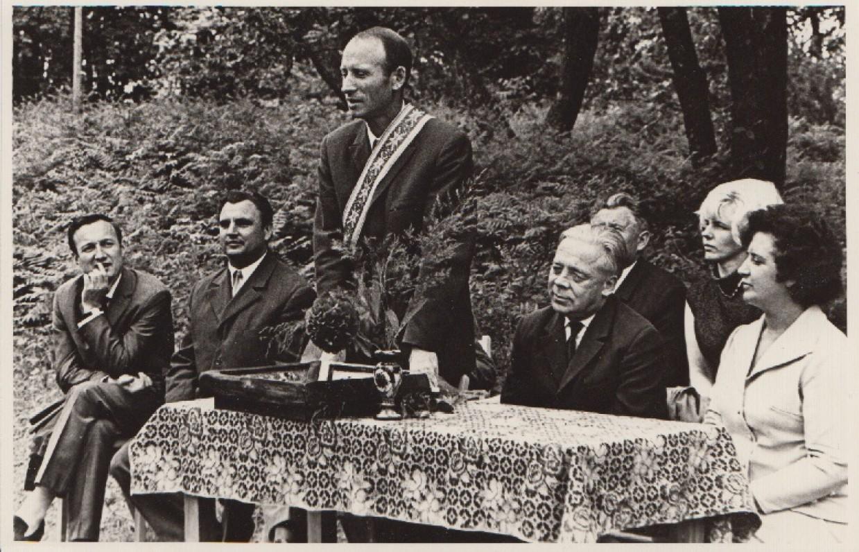 """Už apsakymų knygą """"Merginų sekmadienis"""" M. Sluckis apdovanotas Žemaitės literatūrine premija. Iš kairės sėdi rašytojas A. Pocius, …, stovi M. Sluckis, sėdi poetas A. Jonynas, žurnalistė D. Skersytė ir kt. Ušnėnai, Kelmės r. 1971 m."""