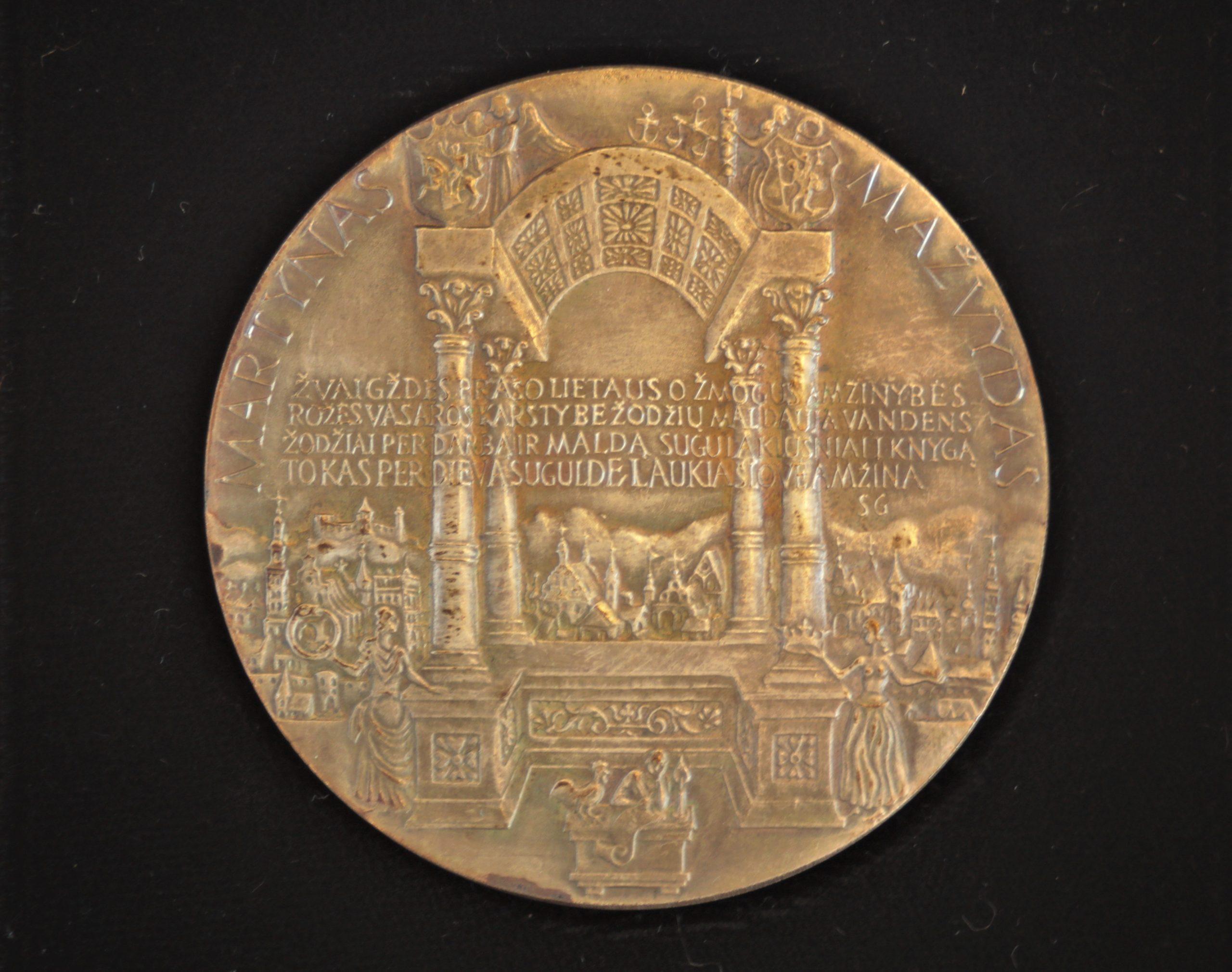Pirmosios lietuviškos knygos 450 metų sukaktuvinis medalis. Metalas. Reversas. Dail. P. Repšys