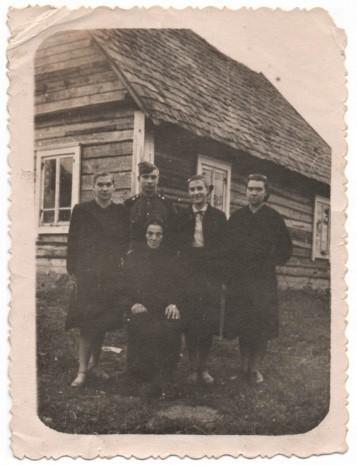 Petriškių kaime, Rokiškio r., prie namų. Sėdi motina Konstancija Šniokaitė-Mezginienė, iš kairės stovi sesuo Genovaitė, brolis Algimantas, Elena ir sesuo Elvyra. 1957 m.